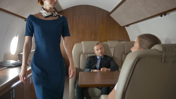Businesspeople inside of private jet speaking with stewardess