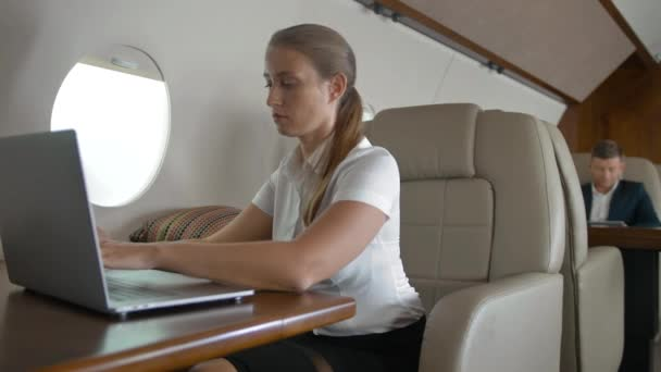 Portrait young woman using modern smartphone at plane,
