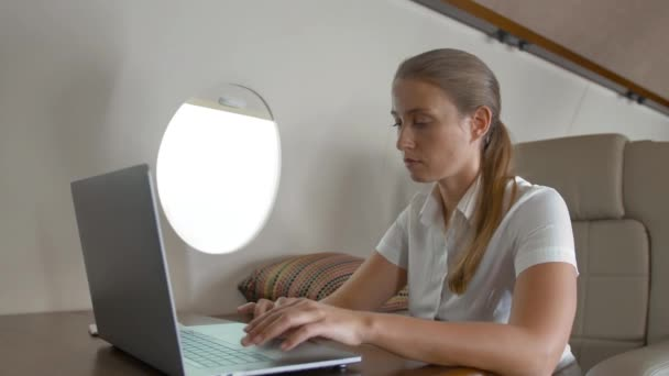 Air hostes asking businesswoman about service inside of private jet cabin. Business lady working at laptop and surfing in internet while aircraft flying.