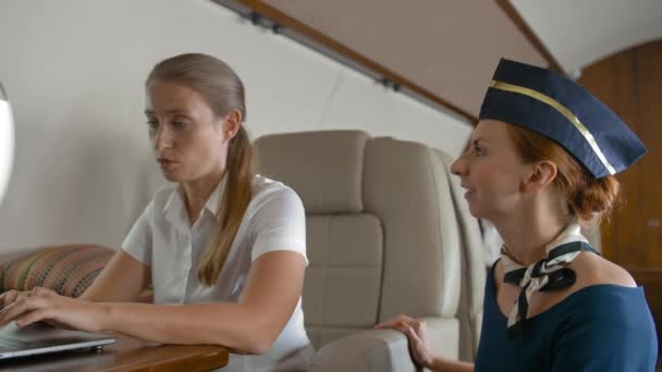 Confident redhair stewardess asking businesswoman about service inside of private jet cabin.