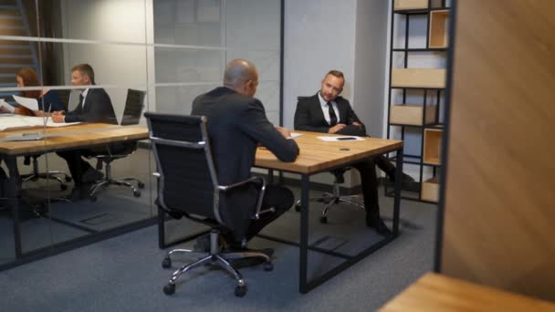 Two Diverse businessmen discussing planning talking during evening briefing at modern boardroom