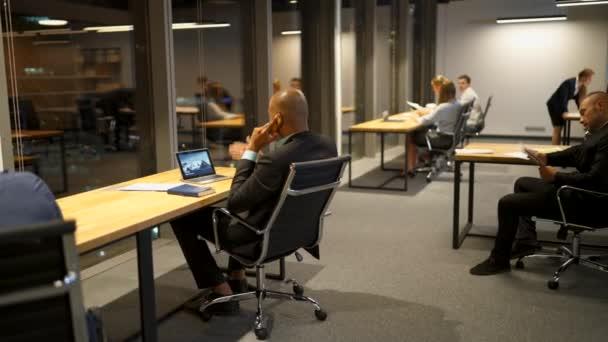 Podnikatelé mluví diskutovat a používat notebooky, tablety a kreslení v kanceláři stůl pozdě v noci