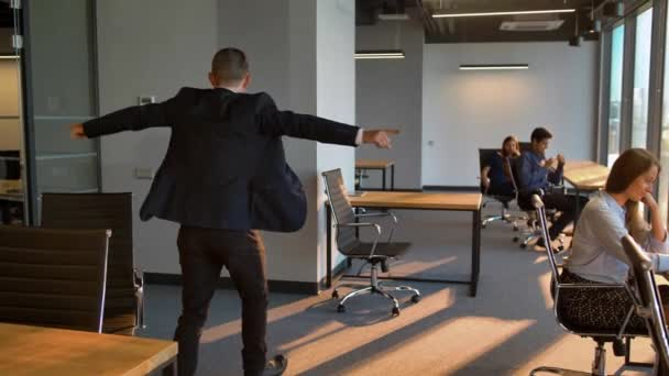 Group of business people looking at dancing male colleague