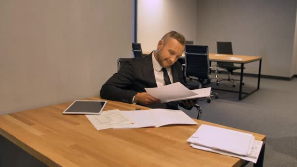 Confident boss entrepreneur working with documents in night office indoor