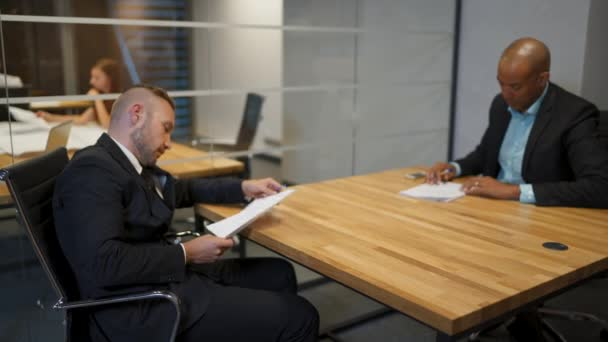 African businessman and his caucasian colleague signing employment contract in office during the meeting