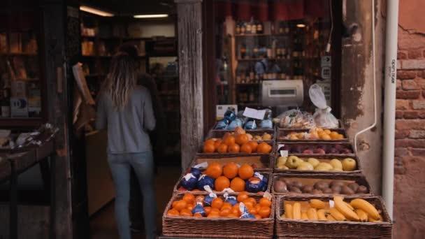 Lidé, kteří přicházejí na pouliční trh s ovocem v Benátkách.