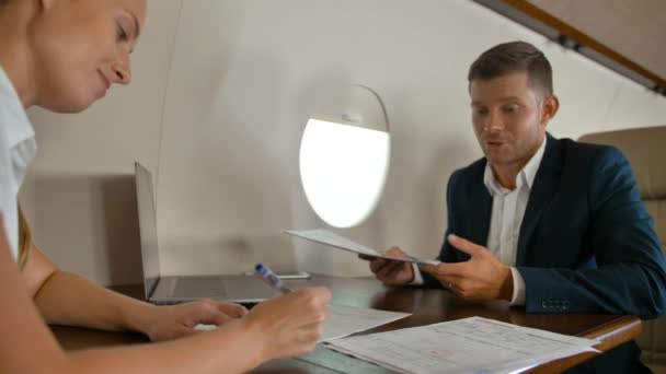 Businessman and businesswoman inside of modern luxury private jet signing big business agreement