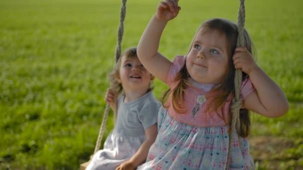 Gesichter zweier Mädchen, die in einem Feld auf einer Seilschaukel in Großaufnahme schaukeln