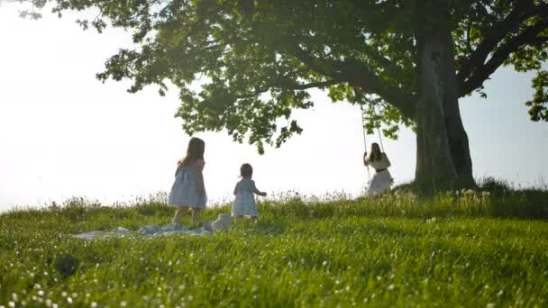 Two little sister girls run across a clean green field to their mother, swinging on a swing.