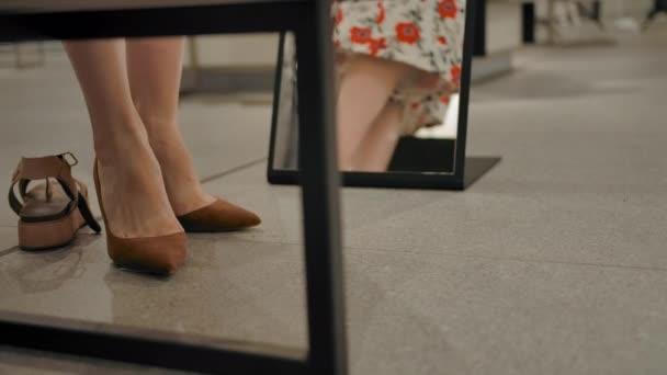 Mladá žena si zkouší boty v obchodě s oblečením za zrcadlem a víří