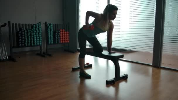 Mladá žena dělá triceps cvičení na sportovních lavicích klečí
