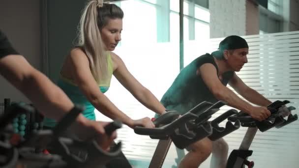 Sportliche Kaukasier, zwei Männer und eine Frau im Fahrradsimulator