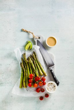 fresh healthy ingredients from green asparagus, cherry tomatoes, tahini and lime sauce on a marble cutting board and a chef's knife
