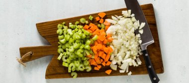 banner of chopped vegetables and a chef's knife on a wooden cutting board. Basic cutting for restaurants or home cooking.
