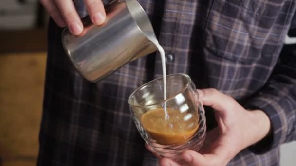 Barista making coffee latte art. Pouring milk into cappuccino.