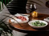 Fából készült asztal marha steak, a saláta és a pohár vörös bor