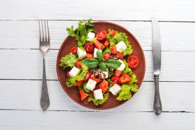 Salad in a plate. Feta cheese, cherry tomatoes, paprika, lettuce. Healthy food. On a white wooden table table. Top view. Free space for text. stock vector