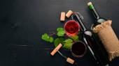 Červené víno v láhvi s sklenici a hrozny. Na černém pozadí dřevěná. Volné místo pro text. Pohled shora.