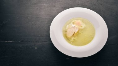 Chicken soup with egg. On the old wooden background. Free space for text. Top view.