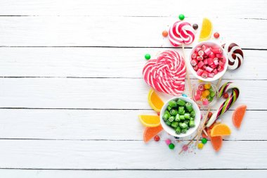 Colorful candies, jelly and marmalade on a white wooden background. Sweets. Top view. free copy space. stock vector
