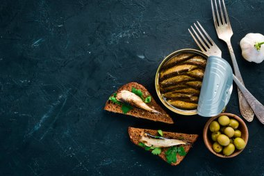 Sandwich with Sprat. Sprat in oil. On a black background. top view. Free copy space.