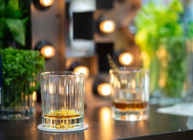 Two almost empty glasses of whiskey on bar counter