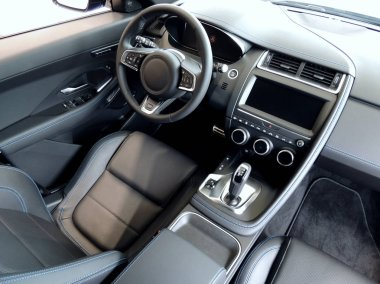 Blue stitched black leather on seats and armrest in car interior