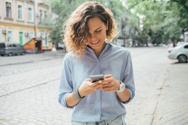 Happy young woman wearing blue shirt using mobile phone and smile on street near road in summer day.