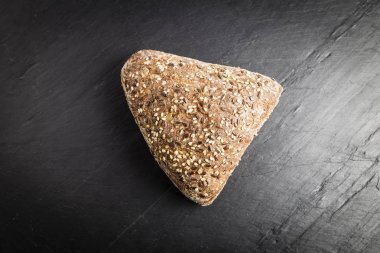 Integral bread in the form of a triangle with linseed, oats and sesame seeds on a black slate table