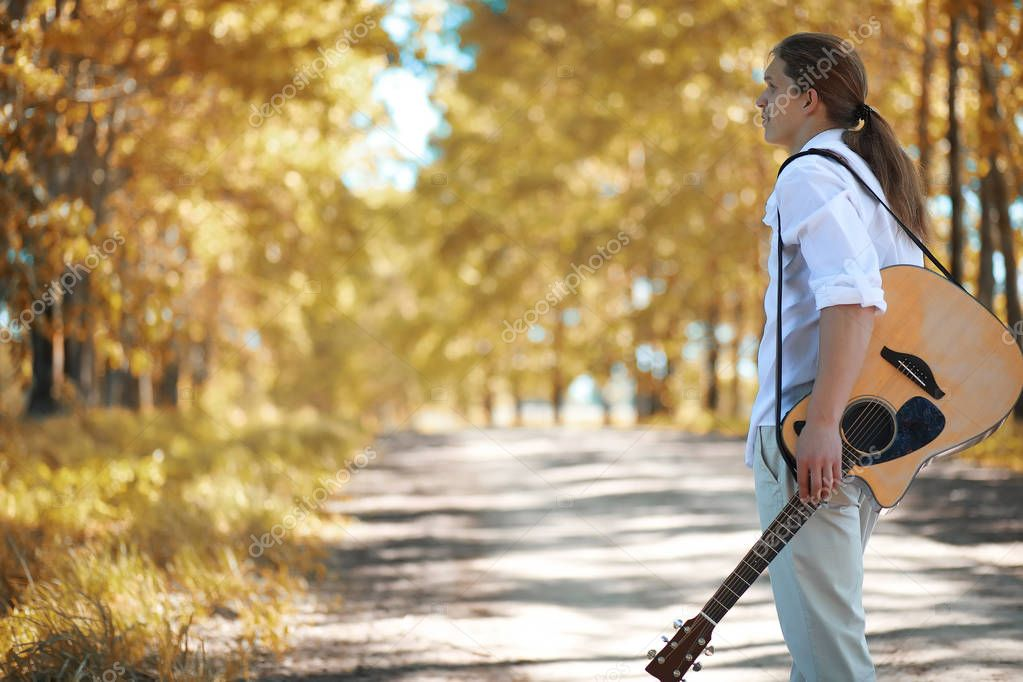 Man with guitar in autumn day