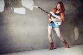 Fiatal vörös hajú lány egy elektromos gitár. Rock zenész lány