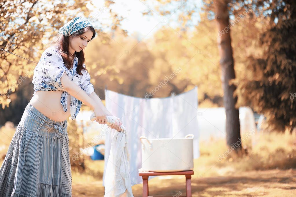 Pregnant woman hanging sheets on the rope for drying