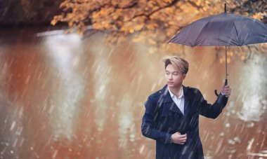 Autumn park in rainy weather and a young man with an umbrella stock vector