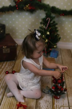 little girl sitting in front of a Christmas tree