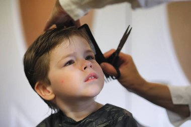 Hairdresser and boy. The boy is doing his hair. Cut hair child i