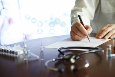 A man signs a medical document. Medical equipment on the table. Stethoscope and ampoules with syringes. Makes notes in office. Medical center.