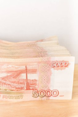 Big stack of Russian money banknotes of five thousand rubles lying on a wooden table