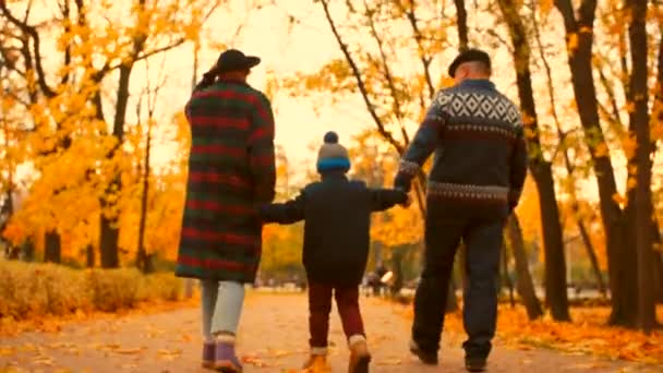Senior couple are having a walk with grandson in the autumn park
