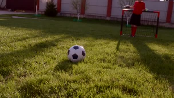 Ragazzini giocano a calcio sul prato nel cortile