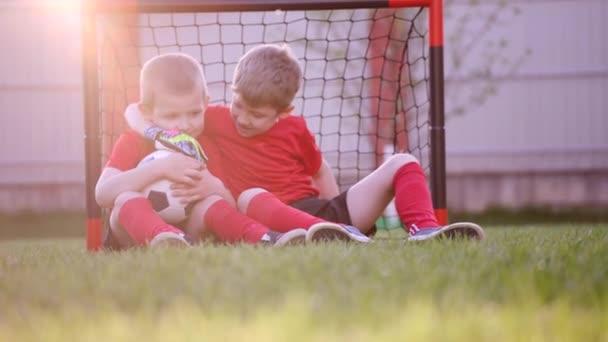 Ragazzini sono seduti allobiettivo calcio sul prato