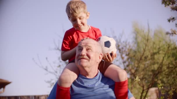 Porträt des Opas mit seinem Enkel am Hals mit Fußball