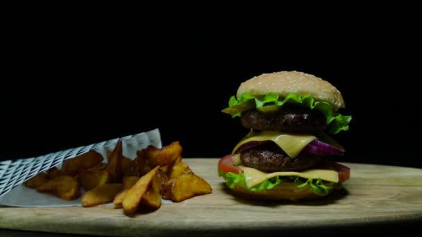 Zblízka se lahodný hamburger s dvojí sýr a hranolky. Černé pozadí