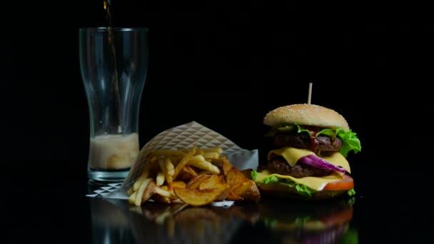 Pommes frites, Burger und Glas mit Coca-Cola auf schwarzem Hintergrund für den kommerziellen Gebrauch