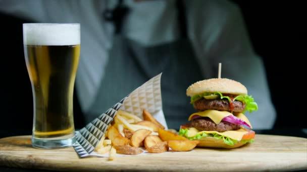 Sada chutné burger, hranolky, pivo na dřevěném podnosu. Kuchař na pozadí