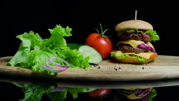 Čerstvá zelenina a chutné burger se sýrem a hovězí kotlety na černém pozadí