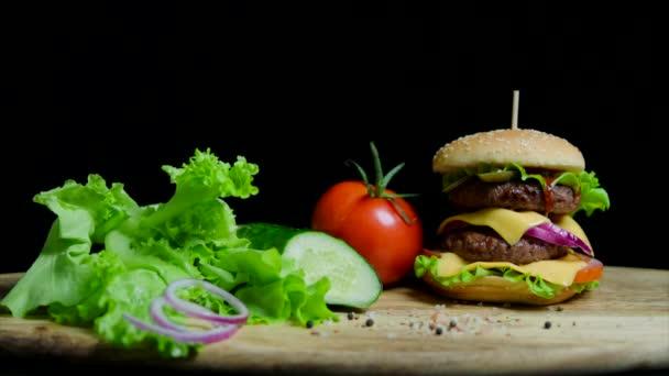 frisches Gemüse und leckere Burger mit Käse und Rinderschnitzeln auf schwarzem Hintergrund