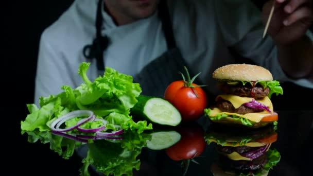 Kuchař, dokončení pikantní hamburger s hovězím masem, sýrem a zeleninou. Černé pozadí pro komerční