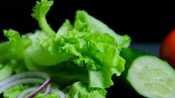 Detailní záběr z čerstvé zeleniny a chutné burger se sýrem a hovězí kotlety na černém pozadí