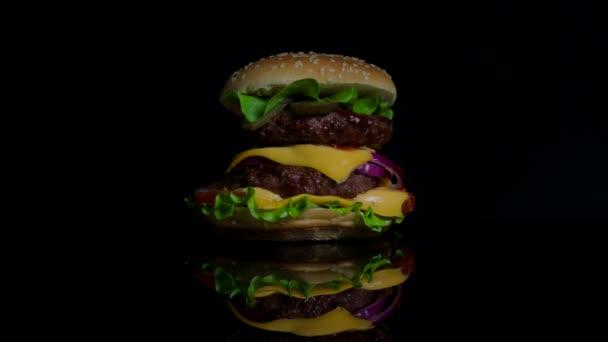 Lahodné horké burger na povrchu černé zrcadlo v ohni. Černé pozadí pro komerční