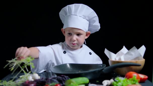 Netter Junge kocht ein Gericht, trägt Kochanzug und Mütze. schwarzer Hintergrund für kommerzielle